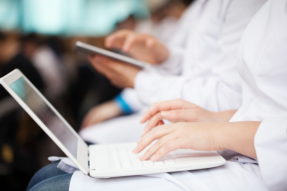 Doctor using Laptop and Tablets for checking Patient Status
