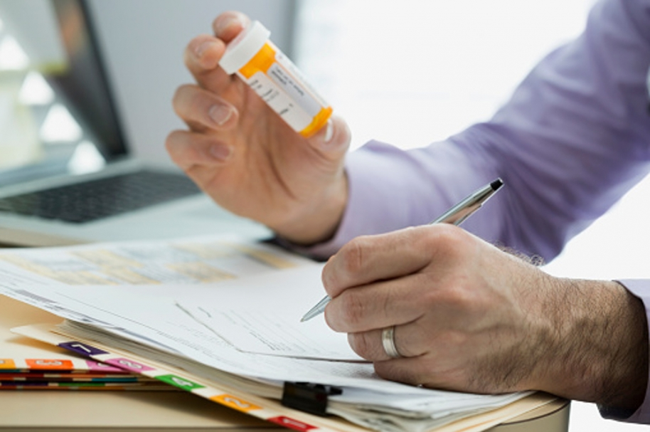 Doctor Analyzing the Medicine and Writing Prescription