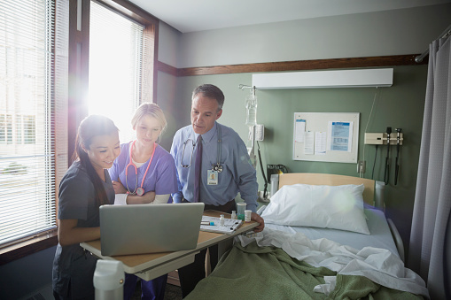 Doctor and nurses using laptop in hospital room