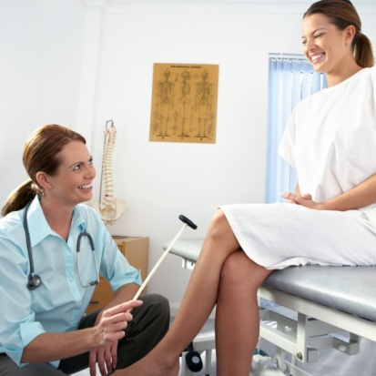female chiropractor testing patient's reflexes in the medical room