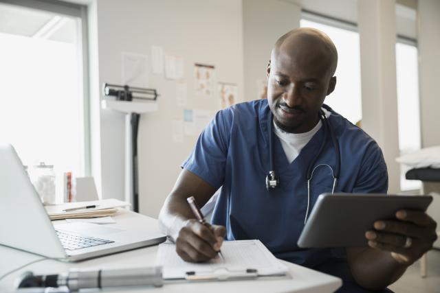 doctor making notes while using EHR on his tablet