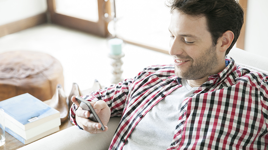 man using smartphone at home communicating with his physician