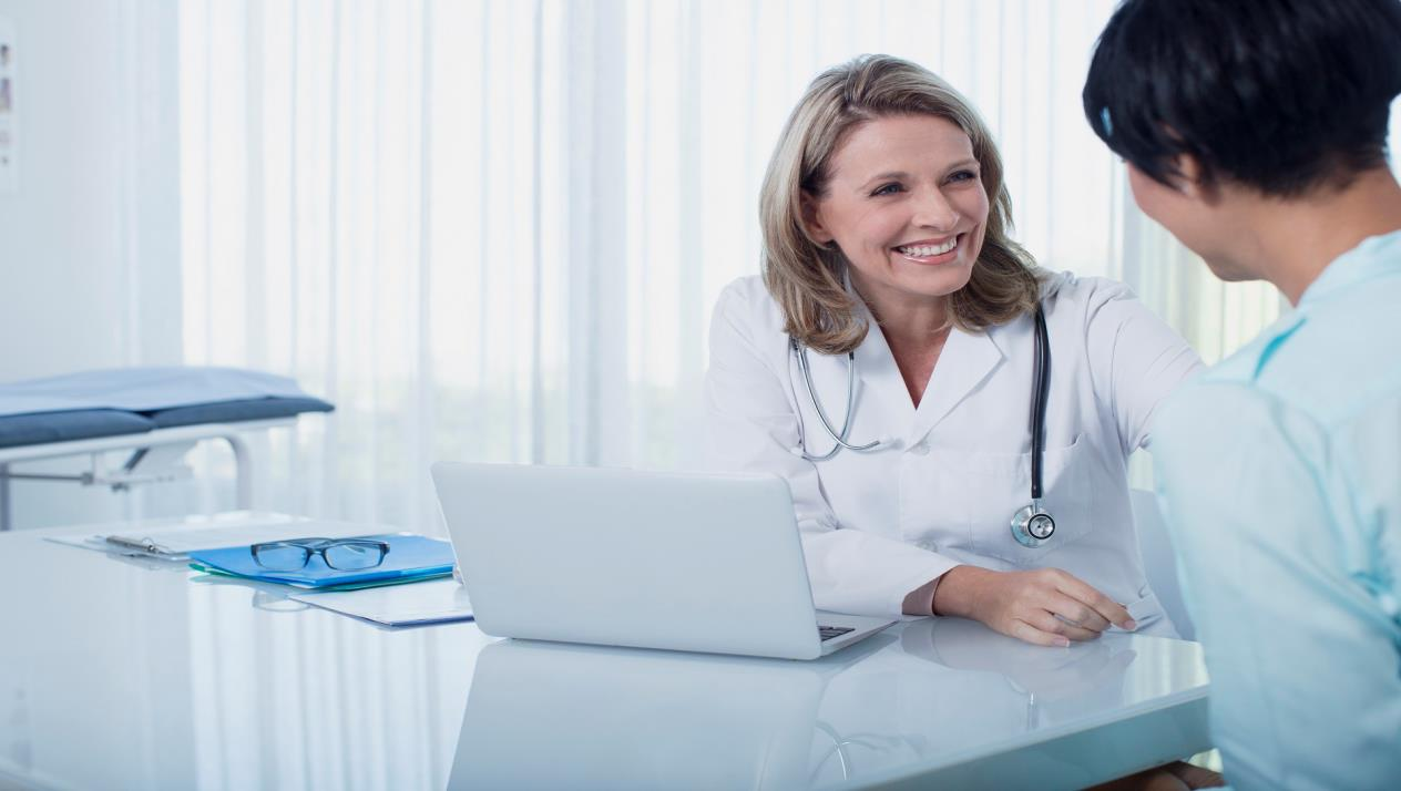 female doctor and woman sitting at desk in office