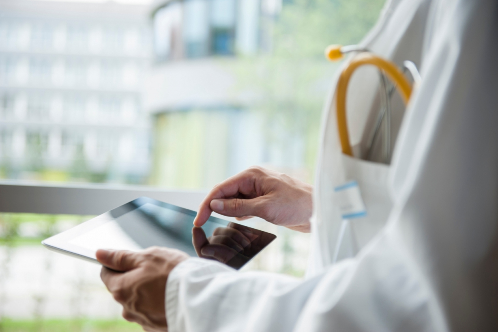 doctor using digital tablet for electronic claim submission through EHR